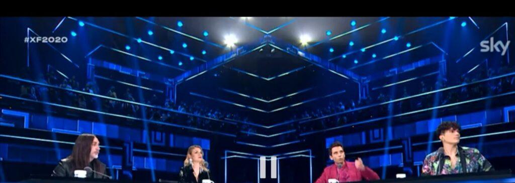 Sopra alle spalle dei giudici di  Factor 2020, nel corso del primo live stagionale presente il pubblico.